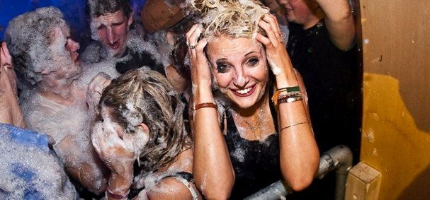 smiling girl at a foam party rubbing foam in her hair